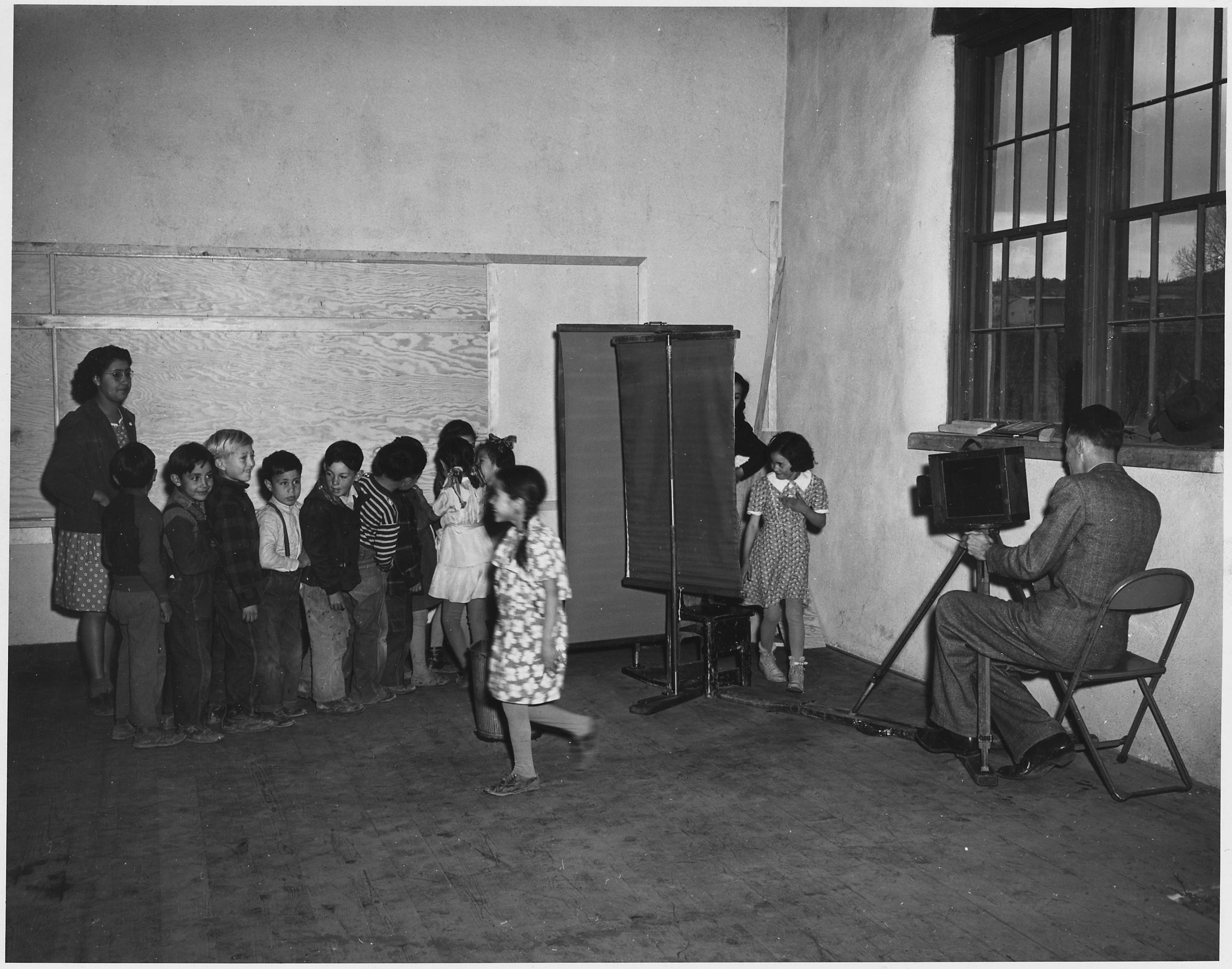Black and white photograph of the corner of an adobe classroom. Children are lined up to have their school pictures taken by a man seated on a metal folding chair, operating his wood box camera on a tripod. Behind the students is a female teacher in polka dot dress and a dark jacket. In the foreground is a young girl with pigtails, walking, slightly blurry from motion. Windows to the right, show a scene with mountains and sky.