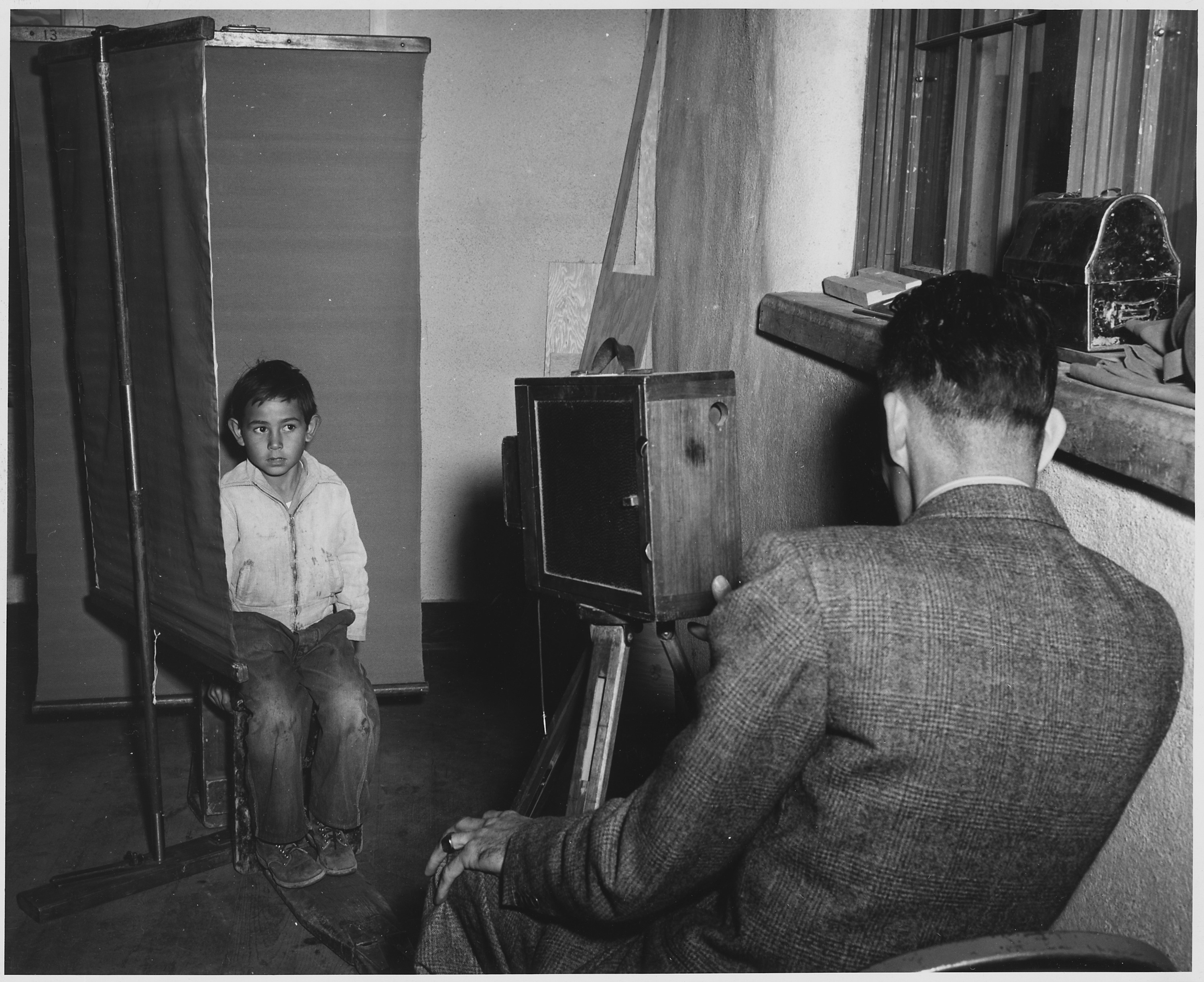 Black and white photograph of boy wearing a light colored jacket and worn out blue jeans, is seated for a photograph in front of a dark photo backdrop. The photographer, a man in a suit is seen from the back, operating a wood box camera on a tripod. To theright is a window with an old fashioned black metal lunchbox resting on the window sill.