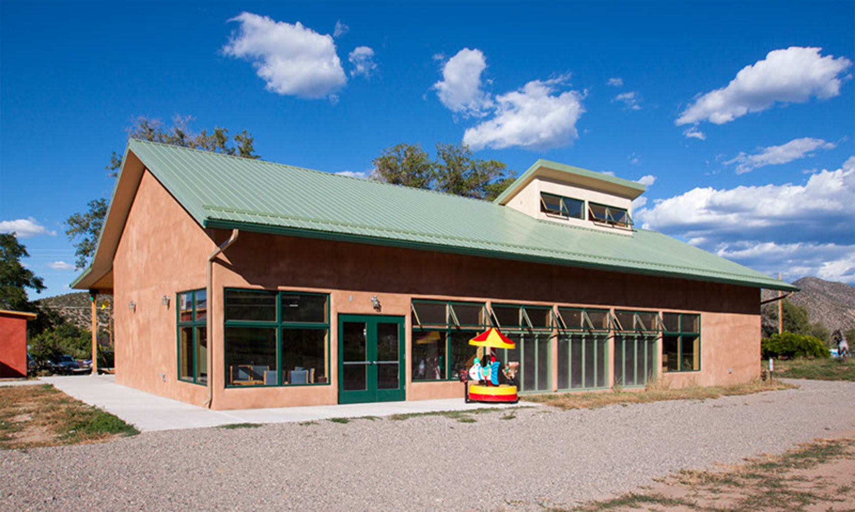 Color photograph of Adobe library building with a plastic children's carousel in bright primary colors in front of the building. In the foreground is a gravel parking lot. Libray building is framed against a bright blue sky with scattered clouds.