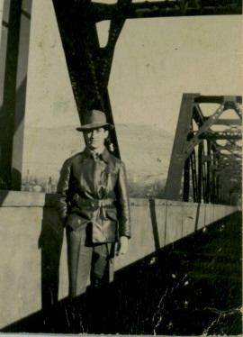 Black and white photograph of a man wearing a leather jacket and a fedora, standing on a black metal framed bridge.