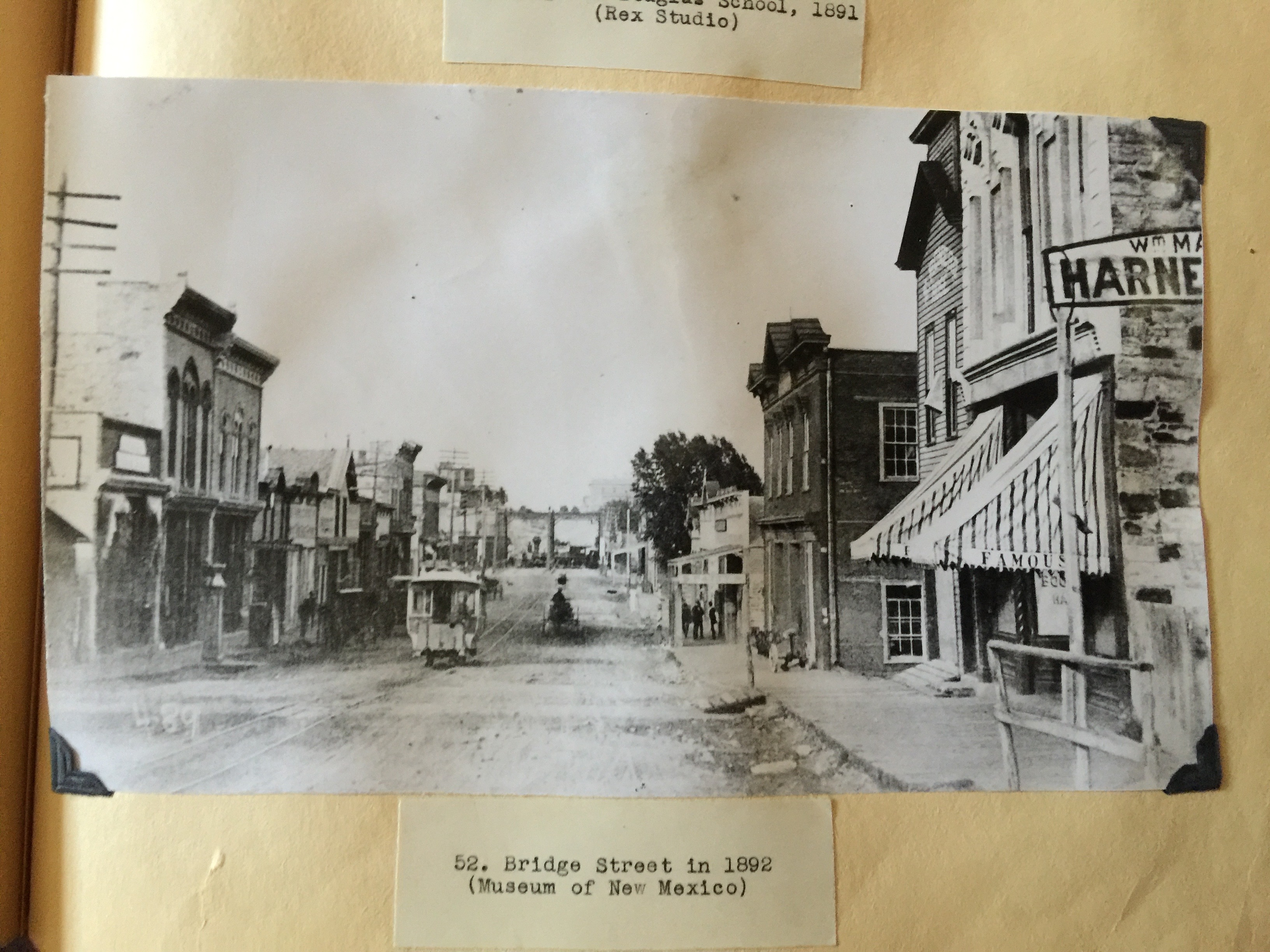 Black and white historic photo of street scene with a trolley car looking towards a bridge in the distance. Photo is glued into a scrapbook and shows warping and discoloration from glue. Beneath photo is a paper tag that reads 52. Bridge Street in 1892 (Museum of New Mexico).