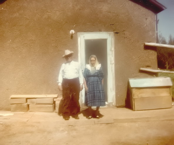 Photo of elderly couple standing front of an adobe structure. The woman, wearing a shawl and a blue dress is framed in a white doorway. The man standing beneath bare porch lamp is wearing a white cowboy hat, white shirt and brown pants.