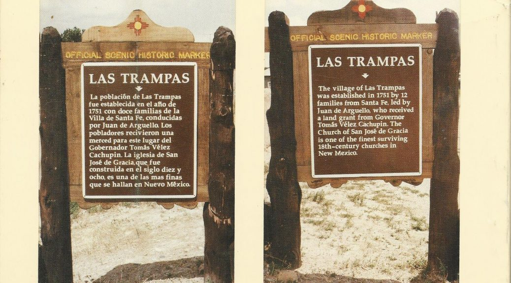 Two photos, side by side, of official scenic markers with historical information printed on metal signage affixed to wood, mounted on rough wooden poles, for the village of Las Trampas. Decorative trim with Zia symbol is attached at the top of both images. The text for the English sign reads: The village of Las Trampas was established in 1751 by 12 families from Santa Fe, led by Juan de Arguello, who received a land grant from governor Tomás Vélez Capuchin. The Church of San José de Gracia is one of the finest surviving 18th century churches in New Mexico. The Spanish sign reads: La poblaciōn de Las Trampas fun establecida en al año de 1751 con doce families de la Villa de Santa Fe, conducidas for Juan de Arguello. Los pobladores recivieron una merced para este lugar del Gobernador Tomás Velez Capuchin. La iglesia de San José de Gracia, que fue construida en el siglo diez y ocho, es una de las las finas que se hallan en Nuevo México.