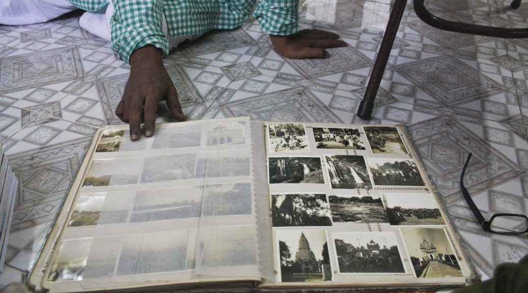 Photo album open to display images, resting on a tile floor near eyeglasses and a chair. A man's hand holds open a page. On the page are black and white photos of scenes of people, buildings and waterfalls.